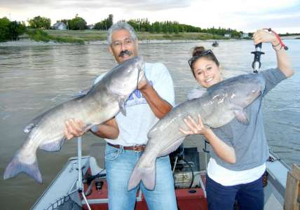 Father and daughter posing with Red River channel catfish
