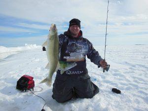 Man on frozen lake ice fishing